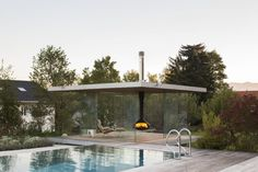 This contemporary glass pool house has uninterrupted views, sliding doors on all sides, a hanging fireplace and a hidden fridge in the floor. Modern Buildings, Interior Architecture, Modern Pool House, Hanging Fireplace, Moderne Pools, Normal House, Glass Photography, Glass Pool, Luxury Pools