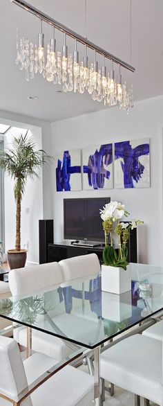 Modern living/dining space. Love the glass table with stainless steel legs, the art adds color & punch to the mostly white room, & finally, that magnificent linear chandelier.   XXXX