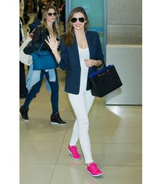 Miranda Kerr's breezy airport style - slouchy blazer over flattering monochromatic white, and a pop of pink in her Reebok sneaks.