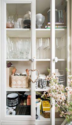 Ikean ovelliseen vitriinikaappiin mahtuu paljon astioita ja muuta pikkutavaraa. Vetimet on ostettu Lillanista.