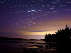 Star trails over a partially frozen Lake George