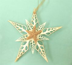 """Large Seashell Ornament - This impressive Christmas Star was formed using cut Seashells and a Starfish. It hangs from a pretty sheer gold ribbon. Approximately 7"""" diameter, ribbon adds 3"""".  ($35.00)"""