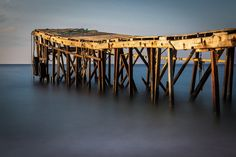 The picture of the wooden jetty and the flat smooth silky water at sunrise – the full edit