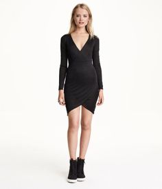 Short, fitted dress in jersey with a slight sheen. Low-cut V-neck and attached, wrap-style bodice section. Long sleeves, seam at waist, and asymmetric hem. Unlined.