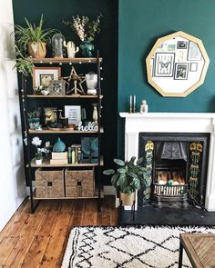homedecor living room Green walls, mirror, sunflower tiles around the fireplace, styled shelf and plants in a living room corner Dark Green Living Room, Teal Living Rooms, New Living Room, Living Room Interior, Living Room Designs, Living Room Decor Green Walls, Feature Wall Living Room, Dark Green Walls, Tiled Wall Living Room