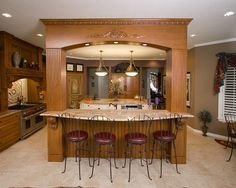 Decorative Arch Over Island That Anchors This Part Of The Kitchen As Well  As Invites Guests