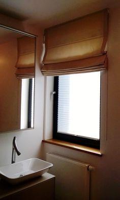 Roleta rzymska dekoruje okno w łazience.