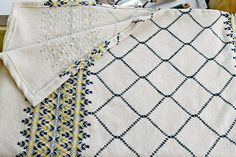 This afghan is hand embroidered with an intricate pattern in a traditional style. This style of work, called huck embroidery or Swedish weaving, leaves little to be seen on the back - just occasional glimpses of color where the threads of the cloth separate. It measures approximately
