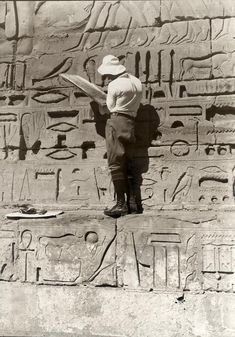 Tourist, interested in cuneiform writing, is copying Egyptian hieroglyphs from the walls of old Egyptian monuments. 1927.