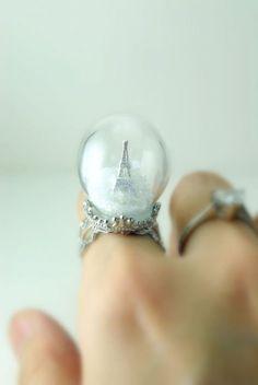 fotografía de anillo con una bola de nieve y una pequeña figura de la torre eiffiel en su interior
