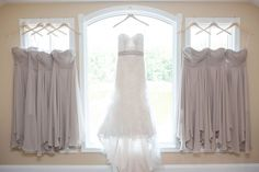 Wedding photo idea: bridal gown in front of the window, with bridesmaids dresses hanging to the sides | Rock Island Lake Club, Northern New Jersey Wedding Venue | Tina Elizabeth Photography