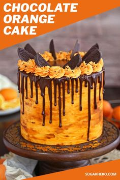 This chocolate orange cake is the perfect blend of citrus flavors and dark chocolate. It features four layers of chocolate cake filled with tangy orange buttercream, topped with a shiny chocolate glaze and chocolate orange slices. #sugarhero #chocolateorangecake #chocolatecake #layercakes #orangecake