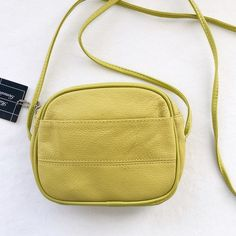 "Sweet little chartreuse leather crossbody bag Yellow-green pebbled leather with bright yellow satin interior. Two large pockets on the exterior--One slip, one zip. Large enough to fit my iPhone 6s and loads of other small items. This is brand new and does have tags attached, but there's no brand. I bought it in a small boutique--it was such a good price for genuine leather, and the color is perfect for spring! Strap drop about 28"". Bags Crossbody Bags"