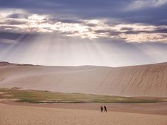 Image: by かがみ~. 鳥取砂丘 Tottori Sand Dunes. Tottori Sand Dunes. Tottori Prefecture, Japan. Sun rays stream down on the Tottori Sand Dunes as people walk along the beach below. Tottori Prefecture, Japan. #beautiful #sands #deserts #Japan #nature #sunrays #photography