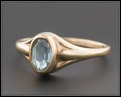 This pretty ring features an aqua blue paste (glass) stone set into a lovely 10k yellow gold mount.  A size 4, this ring would be a perfect gift for a young girl or a lovely pinky ring for a woman with slender fingers. The ring is marked for 10k and weighs 1 gram. It is in very good condition; however, there is some minor wear to the table of the paste stone (visible only upon magnification).  We can resize most rings free of charge. If a different size is desired, please contact our store…