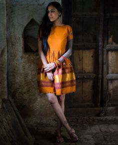 This box pleated mango-orange dress has been crafted from a handwoven tribal Rabari shawl fresh off the loom from Bhujodi Village in Kutch, India. This shawl ta