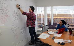 Student at whiteboard in small group study area at NCSU Hunt library.