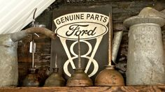 Rusted antique oil cans and gas cans in front of antique Ford V8 sign