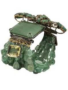 Emerald statement bracelet in green from Iradj Moini. This fluorite statement bracelet features a large green emerald, a smokey topaz citron, strands of fluorite stones, and a bar fasten. Converts into a pin.