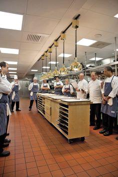 John Folse holds a kitchen staff meeting around the runners' station in the kitchen. - Sara Essex Bradley