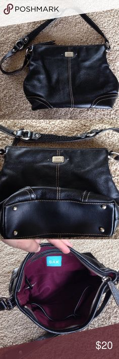 The Sak Black Leather Bag Closet staple black leather shoulder bag by The Sak.  This bag has silver tone hardware and an eggplant colored cotton lining with two interior pouches and a zipped pocket as well as a small exterior pocket on the back side.  Excellent used condition, super soft leather. The Sak Bags Shoulder Bags