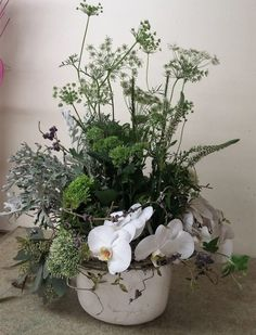 low centerpiece.  green and white flower arrangement.  White cymbidium orchid, green buttons, queen anne's lace, dusty miller, while trachelium, seeeded eucalyptus