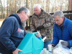 Ricky Howell (center) watches as Roanoke Canal Commission Chairman Mike Green pours water into a cup held by Commission Secretary Chris Wicker.