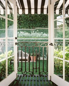November 2012 Issue Photo - French doors leading to a balcony covered by a black-and-white-striped awning