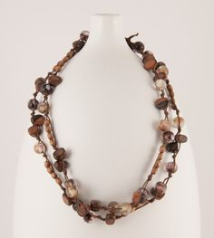 Long, bohemian necklace, hand knotted using waxed cotton cording, lampwork beads in beige and brown and two types of natural wood beads. The clasp is made from a hand-tied loop that fits around a bead. $24 By Artigiana Designs