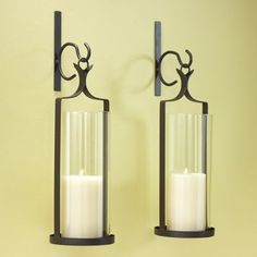 Set of 2 Wall Sconces from Country Door. Fill the room with rustic style. Glass candle shade; metal frame with a brown painted finish.