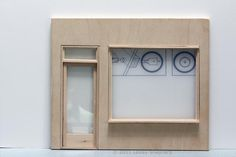 Fit a non opening window into the front of a dolls house scale or model shop using craft wood and plastic sheet.