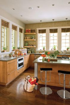 """Kitchen without upper cabinets - Idea House Kitchens - Southernliving. What's a kitchen without upper cabinets? """"Clean and casual,"""" says team interior designer Traci Kearns. """"Because there's a bevy of surrounding windows that also contain a lot of mullions, upper cabinetry would have completed with this look.""""  Tiers of cantilevered shelves get the job done. For stowing away cookware, a central island provides more storage and separates the kitchen from the adjacent dining room and family…"""