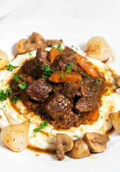 """Your Tuesday NEEDS this hearty comfort dish. Just trust me, it does. I was feeling a little Julia Child-inspired, so I decided to make her famous beef bourguignon. But, I didn't stop there, I also made her garlic mashed potatoes (which just may be the best I've had). Sooo, just FYI, this is not a meal that you can just """"whip up."""" It will take hours, but it will be worthevery second. Plus, it makes at least 6 servings, so you can enjoy the fruits of your labor for the whole week! For real…"""