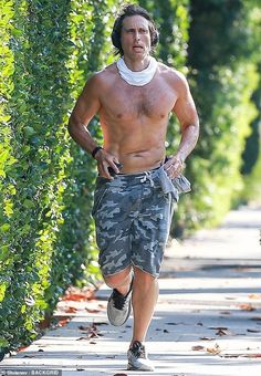 Camo chic: The 49-year-old rocked a pair of cotton camouflage shorts with some gray traine... Camouflage Shorts, Old Rock, Falling In Love Again, Man Crush, Jogging, Crushes, Sporty, Pairs, Gray