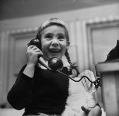 A young girl talking to Santa Claus on the telephone. 1947.