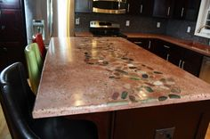 Concrete Countertops, Concrete Countertops with river rock inlayed, double basin sink, and drainboard attached. Glass mosaic backsplash wit...