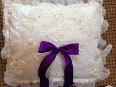 Ring pillow with purple accent bow. The lace was taken from my daughters wedding gown to make this pillow for her daughters wedding. It is a really neat concept.