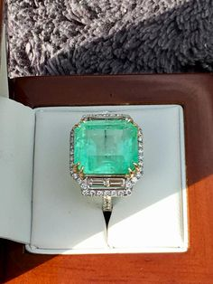 ~This Emerald is from theMines of Muzo, Colombia famous for their distinct Colored Emeralds.The Emerald was Cut by a multi generation cutter inMiami'sFamousSeyboldBuilding.TheEmeraldweighs roughly 16 carats &is set in a Beautifully Designed Platinum Ring with 18K Yellow Gold prongs. The Side diamonds are baguettecutVS diamonds weighing about 1ct which are surrounded by round brilliants weighing an additional 2/3 ct.