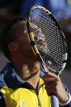 France's Jo-Wilfried Tsonga puts his racket to his head in his quarterfinal match against Switzerland's Roger Federer at the French Open tennis tournament, at Roland Garros stadium in Paris, Tuesday June 4, 2013. Tsonga won in three sets 7-5, 6-3, 6-3. (AP Photo/Petr David Josek)