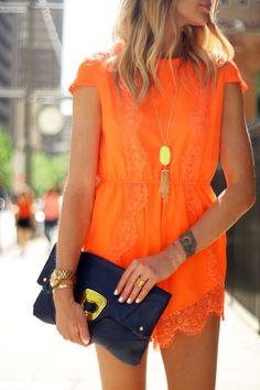 Orange lace dress w navy clutch.