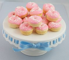 A photo of Baked White Chocolate Cake Doughnuts with pink Vanilla Doughnut Glaze decorated with white nonpareils on a white cake stand.