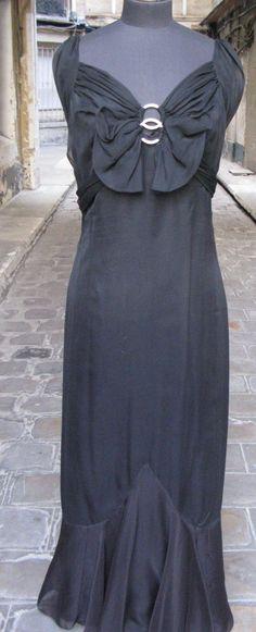 """LOUISE BOULANGER Robe du soir vers 1930. Mousseline de soie noire, corsage drapé dans des anneaux de strass imbriqués formant un noeud sur le devant profondément décolleté derrière. Volant monté en pointe sur le bas de la jupe. Griffée """"Louise Boulanger Champs Elysées / 3 rue de Berri / Paris"""" n° 5672"""