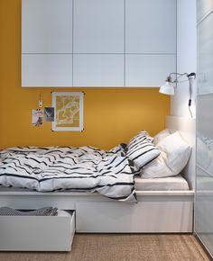Lähikuva IKEA-sängystä, jonka alla on säilytyslaatikot. Sängyn yläpuolella kaappeja.