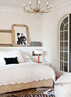 White bedroom with orange table lamp and zebra hide rug