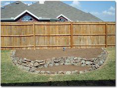 Rock edged flower bed/ retaining wall.  Like the two different heights, also on site a picture of bed planted.