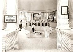 """A group of guests 'taking the waters' at the infamous Pluto Spring behind the French Lick Springs Hotel.  The sign on the left pillar reads """"NOTICE - All persons not guests of the French Lick Springs Hotel must present Water Tickets to the attendant""""."""