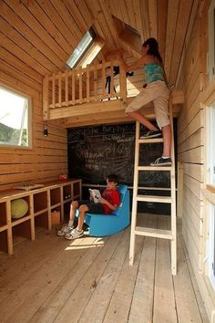 Playhouse is 8 by 9 feet. Built-in cubbies offer plenty of storage for games, toys and other play equipment. A large chalkboard provides a spot for playing school, hosting club meetings and drawing. The blue rocking chair is made of recycled milk bottles. Windows and skylights naturally light the space, but there are also crank lights and a crank radio.