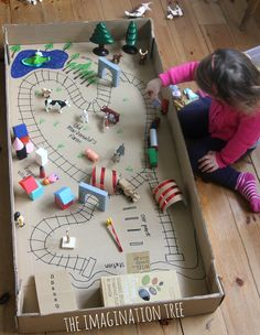 DIY: Cardboard tunnels, cereal box train station and train tracks drawn in a giant box!