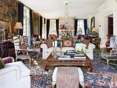 In the living room, matching 19th-century Louis XV–style wing chairs flank an 18th-century Chinese carved low table; pillows made from antique textiles accent the sofa, and the throw in the foreground is a 19th-century Kashmiri paisley.