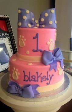 Chic pink 2-tiered birthday cake made with buttercream icing and purple fondant bows.